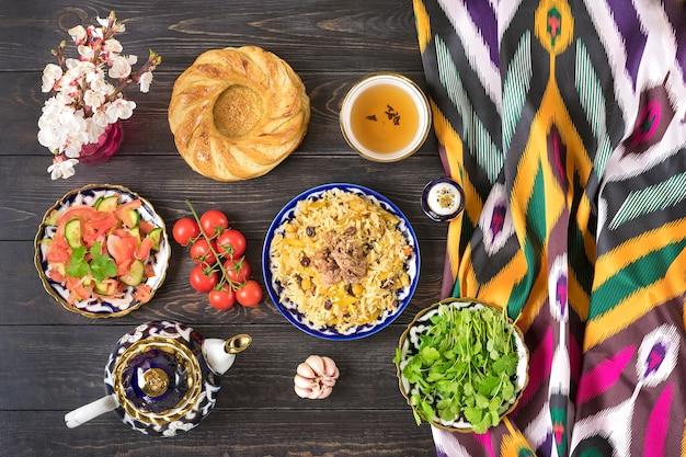 Национальный узбекский плов с мясом, ачичук салат из помидоров, огурцов, лука в тарелке с традиционным