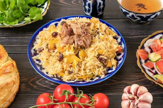 National uzbek pilaf with meat, achichuk salad of tomato, cucumber, onion in plate with traditional pattern, cilantro, cherry tomatoes, garlicbread tortilla - patir on dark wooden table top view