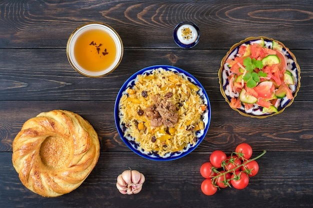 National uzbek pilaf with meat, achichuk salad of tomato, cucumber, onion in plate with traditional