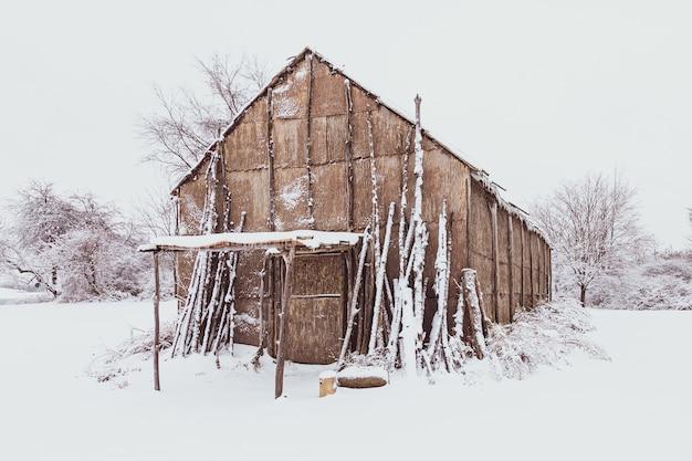 冬の間白い雪で覆われた地面を持つネイティブアメリカンのロングハウス