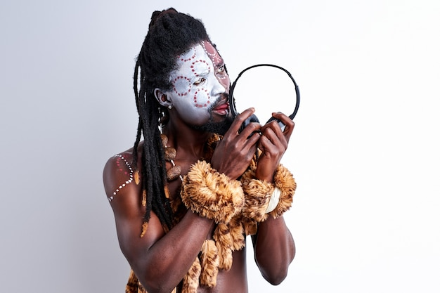 Native man tastes headphones, licks it, use it incorrectly. male in ethnic aborigen wear isolated over white wall