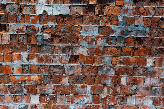 Естественный абстрактный текстурированный фон заброшенной красной кирпичной стены.