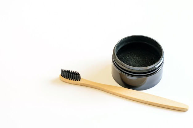Natural activated charcoal and bamboo toothbrush for teeth whitening on the white