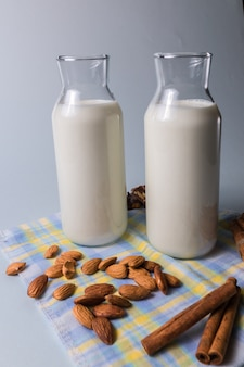 Natural alkond milk in bottles with almond nuts and cinnamon sticks on napkin
