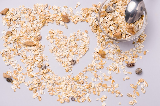 自然で健康的な朝食。灰色の背景にハートの形をしたミューズリー。