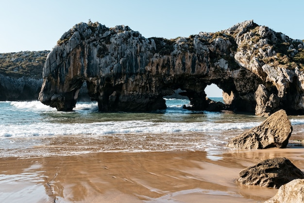 Natural arch from rocks in the water near the shore on a clear day