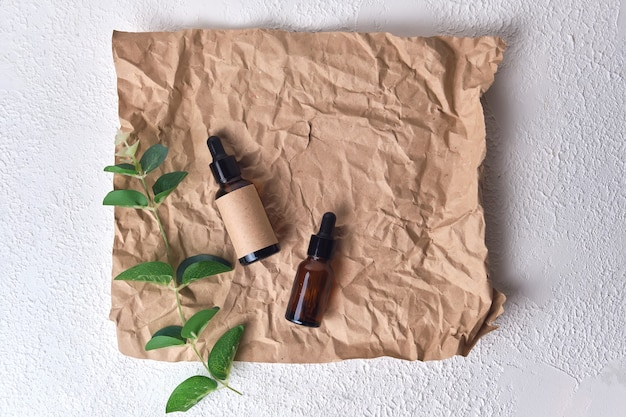 Natural aroma oil in an amber glass brown dropper bottle on crumpled paper on white textured background. organic beauty product packaging design