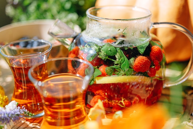 Natural aromatic fruit tea in a transparent teapot and in a cup among berries and flowers. warming aromatic tea with a deep aroma of berries and wildflowers.