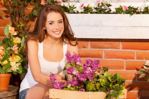 Натуральные, как эти цветы. красивая молодая женщина устраивает цветы в горшке и улыбается в камеру, сидя возле дома