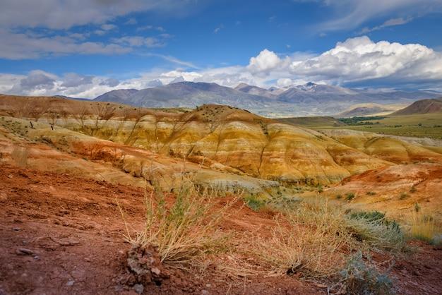 알타이 산맥의 자연적인 매력, 화성의 풍경. 흰 구름이 있는 푸른 하늘을 배경으로 바위 능선이 있는 멋진 파노라마. 러시아의 인기있는 관광 루트.