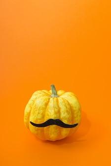 주황색 배경에 콧수염이 있는 천연 정통 호박. 단색 색상. 할로윈 초현실적인 얼굴 개념