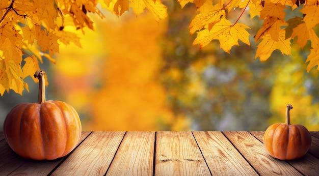 コピースペースと木製の素朴なテーブルに葉とカボチャと自然秋の背景。