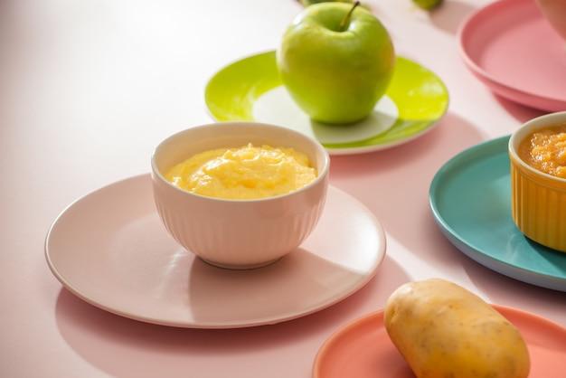 Концепция естественного детского питания. различные виды овощного пюре на светлом фоне