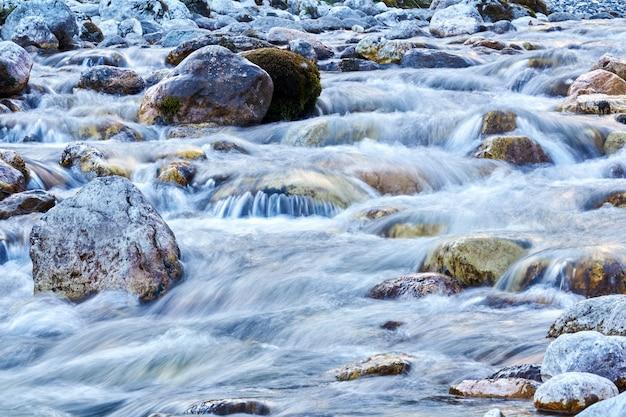 自然の背景-澄んだ山の川のクローズアップの岩の浅瀬、動きのある水がぼやけている