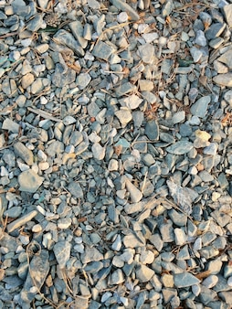 Естественный фон из мелких камней, гальки, песка и натуральных веток, вертикальная рамка.