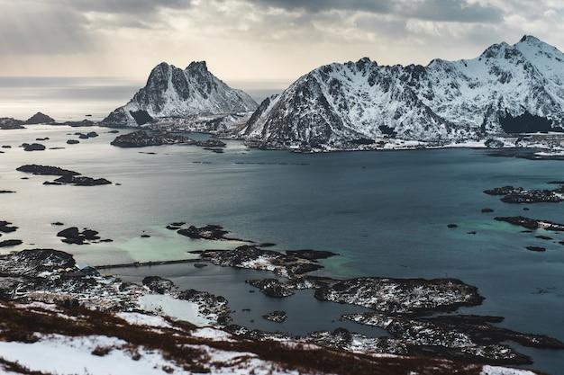 ノルウェーの冷たい海と雪に覆われたロッキー山脈の自然の背景。上からの魅力的な眺め。自然の美しさと冬時間の概念