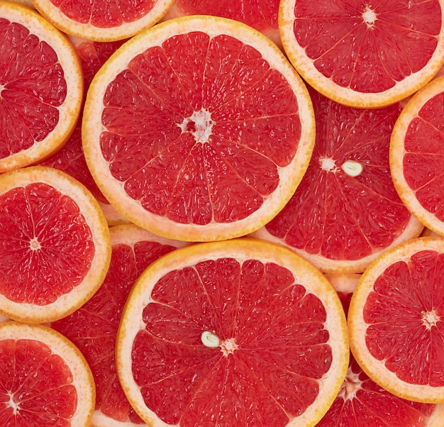 The natural background of red ripe round slices of grapefruit