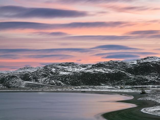 Естественный фон. вечернее небо. линзовидные облака над заснеженными холмами арктики. кольский полуостров. териберка.
