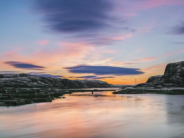 Естественный фон. вечернее небо. линзовидные облака над заснеженными холмами арктики. кольский полуостров.