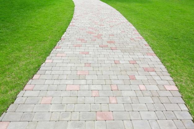 뒤뜰의 잔디밭 골목 사이에 자갈이 깔린 자연 배경 도로