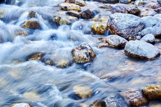 自然の背景-岩だらけの渓流の水の流れは動きがぼやけています