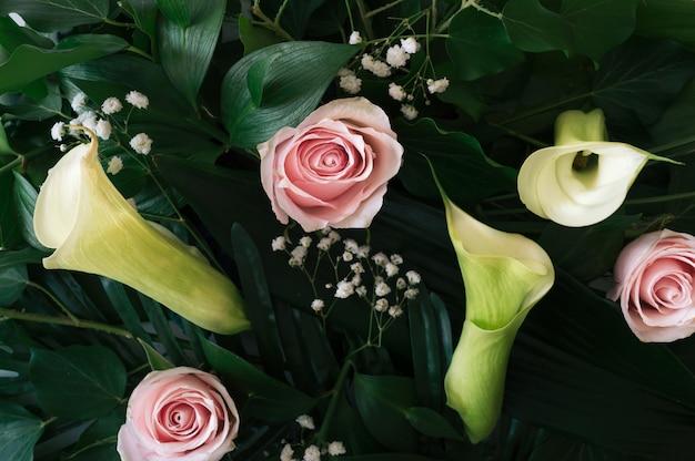 Естественный фон с сочетанием разных видов листьев, тропических пальм и цветов розы и каллы.