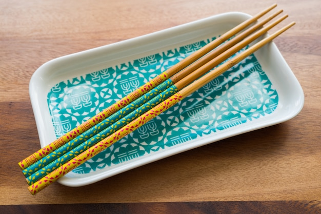 Natural bamboo chopsticks and plate on wooden table background