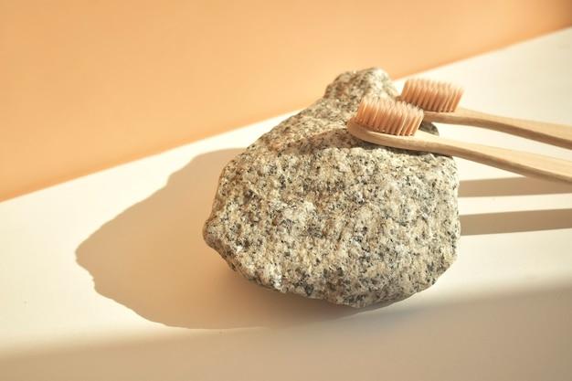 Зубная щетка из натурального бамбука на белом фоне с декором из натурального камня и цветов. без пластика основы, стоматологическая помощь. концепция нулевых отходов.