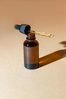ダークガラスの無印のスポイトボトルにハーブエキスを配合した天然のバウティオイル。ブランドのモックアップ。