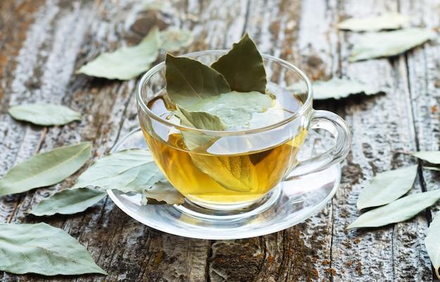 素朴な木製のテーブルの上のガラスカップの天然月桂樹の葉ハーブティー