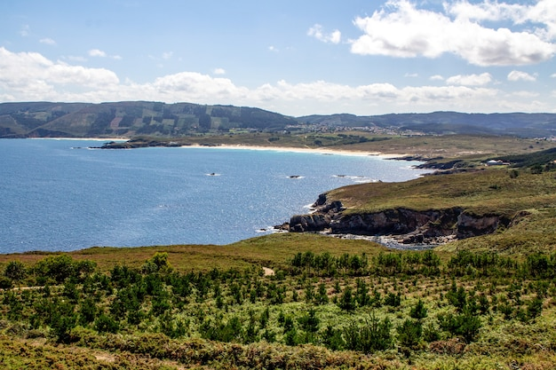 Natural bay with calm water surrounded by mountains on a sunny day in galicia, spain
