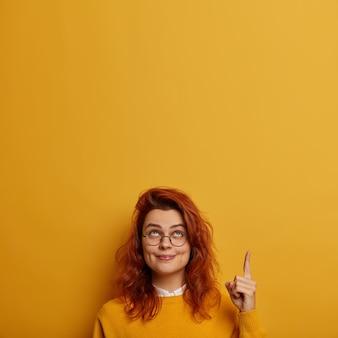 Натуральная красивая девушка-промоутер демонстрирует скидки, приятное предложение, пустое место вверх, показывает указательный палец вверху, улыбается с ямочками на щеках.