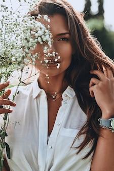 自然の美。花で顔を覆い、屋外に立ってカメラを見て魅力的な若い笑顔の女性