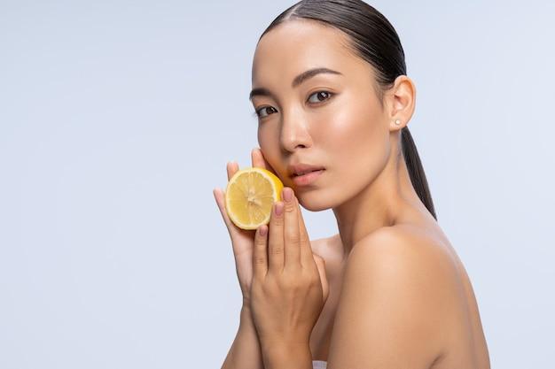 Естественная красота. веселая брюнетка модель держит лимон обеими руками, позируя на камеру