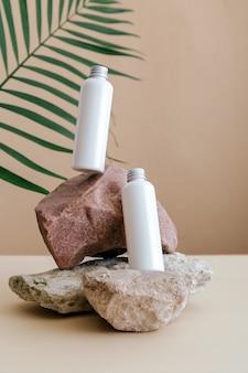 천연 미용 화장품 병은 야자수 잎이 있는 돌 받침대 베이지색 바탕에 스킨케어를 위한 흰색 모의 화장품입니다. 천연 스킨 바디 케어 로션 병 공중 부양 흰색 화장품 병.