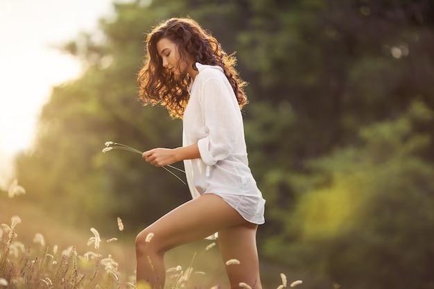 Девушка естественной красоты вокруг цветов на открытом воздухе в концепции наслаждения свободой.