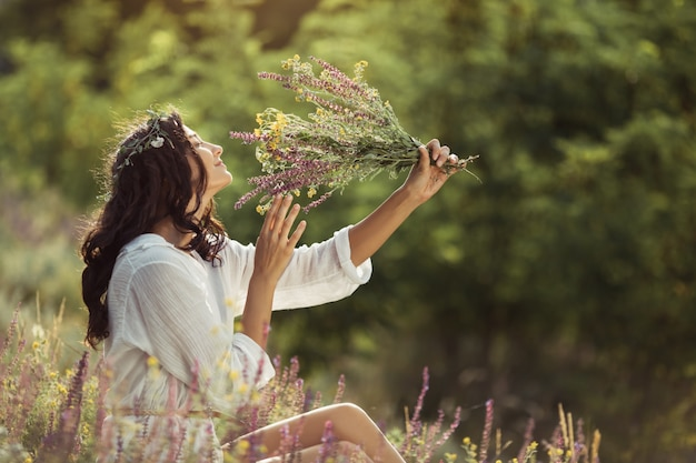 Natural beauty girl with bouquet of flowers outdoor in freedom enjoyment concept.