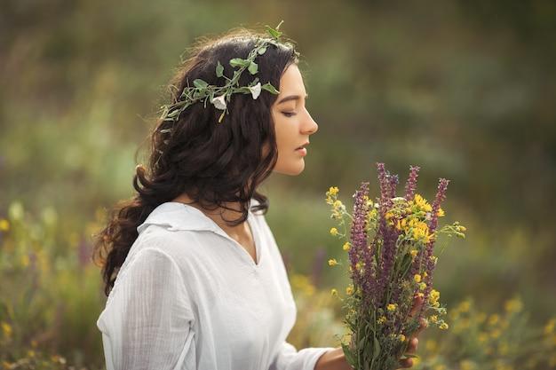 Девушка естественной красоты с букетом цветов на открытом воздухе в концепции наслаждения свободой. портретное фото
