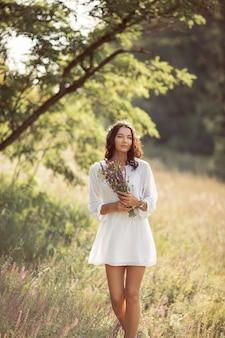 Девушка естественной красоты с букетом цветов на открытом воздухе в концепции наслаждения свободой.