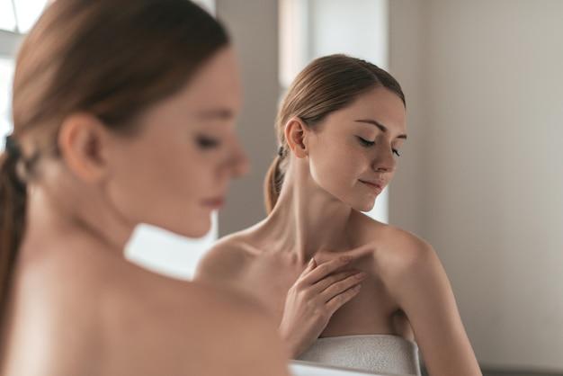 Естественная красота. вид через плечо молодой женщины, касающейся ее кожи и смотрящей в сторону, стоя перед зеркалом