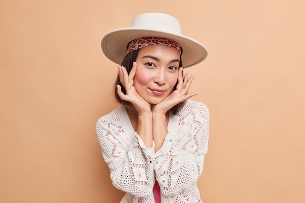 自然の美しさの人々とファッショナブルなコンセプト。魅力的なアジアの女性が優しく顔に触れる