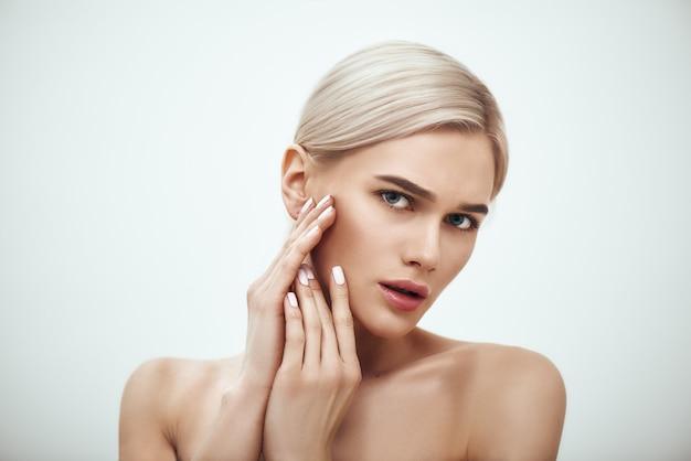 Портрет естественной красоты великолепной блондинки, касающейся ее идеальной мягкой кожи стоя
