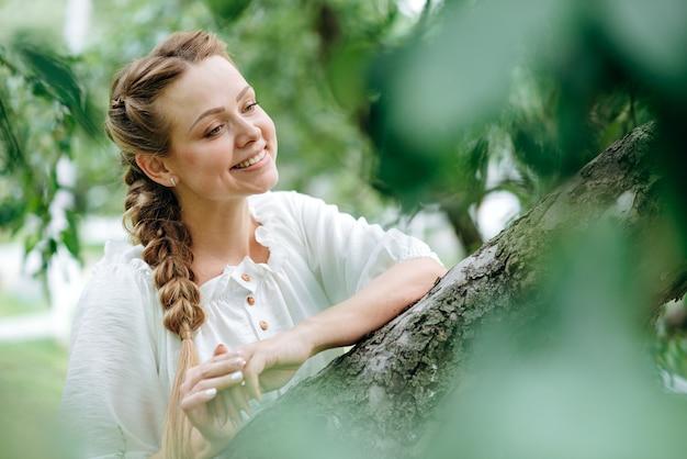 자연미. 푸른 잔디가 있는 들판에 서서 신선한 공기를 마시며 웃고 있는 여성의 초상화. 야외에서 포즈를 취하는 행복한 어린 소녀