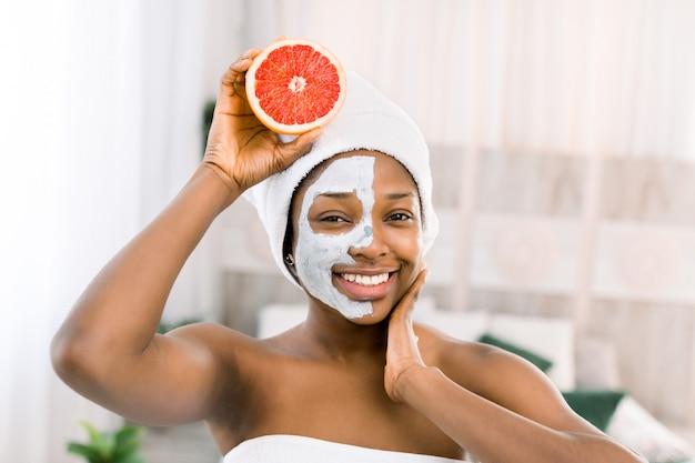自然の美しさ、スパ、健康的な肌のコンセプト。白いタオルでアフリカ系アメリカ人の喜んでいる女性、グレープフルーツを保持している、顔に泥マスクでこぼれるような笑顔