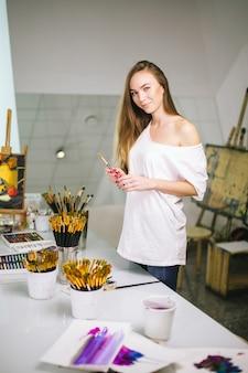 Естественная учительница красоты в своей студии готовится к художественному уроку