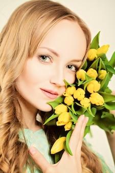 자연스러운 금발의 아름다움. 노란 튤립 꽃을 가진 여자