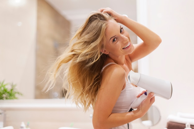 Natural blonde woman drying hair in bathroom
