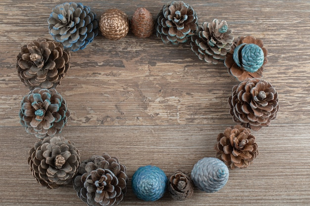 Natural blue and golden colored oak tree cones on a wooden deck