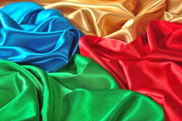 Натуральная синяя, красная, золотая и зеленая текстура атласной ткани