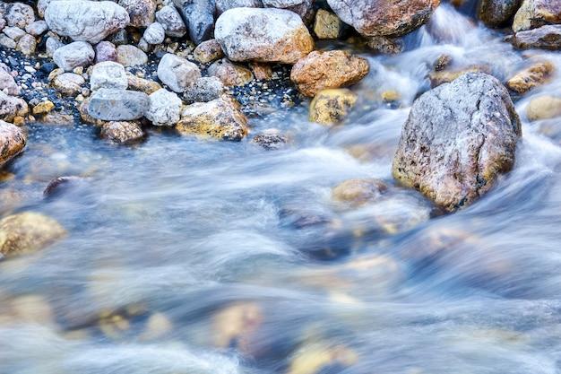 自然なぼやけた背景-岩山の川の水の急速な流れ